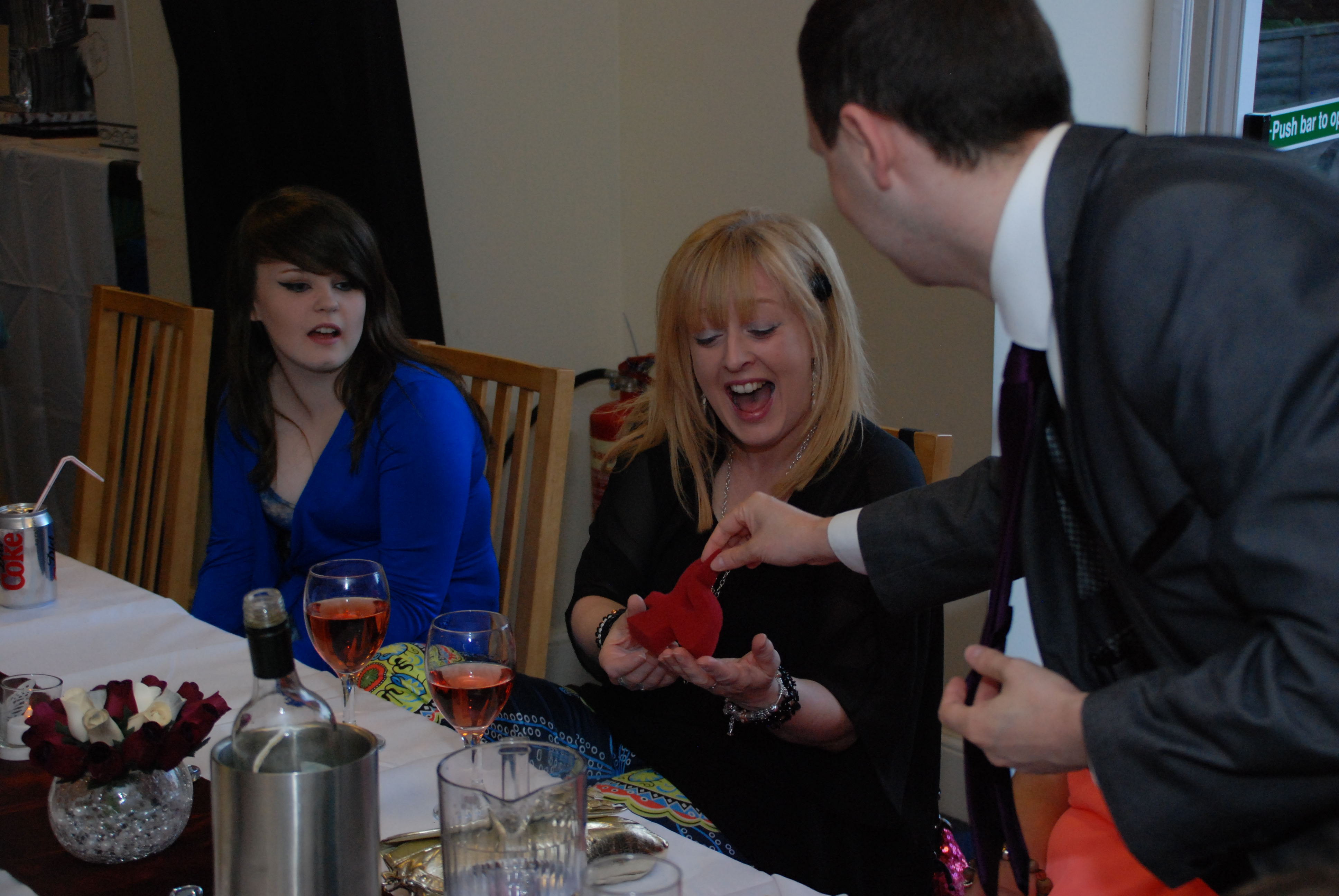 Kilmarnock Magician Steven Blair performing close-up magic for a group at an event either a Wedding or Party.